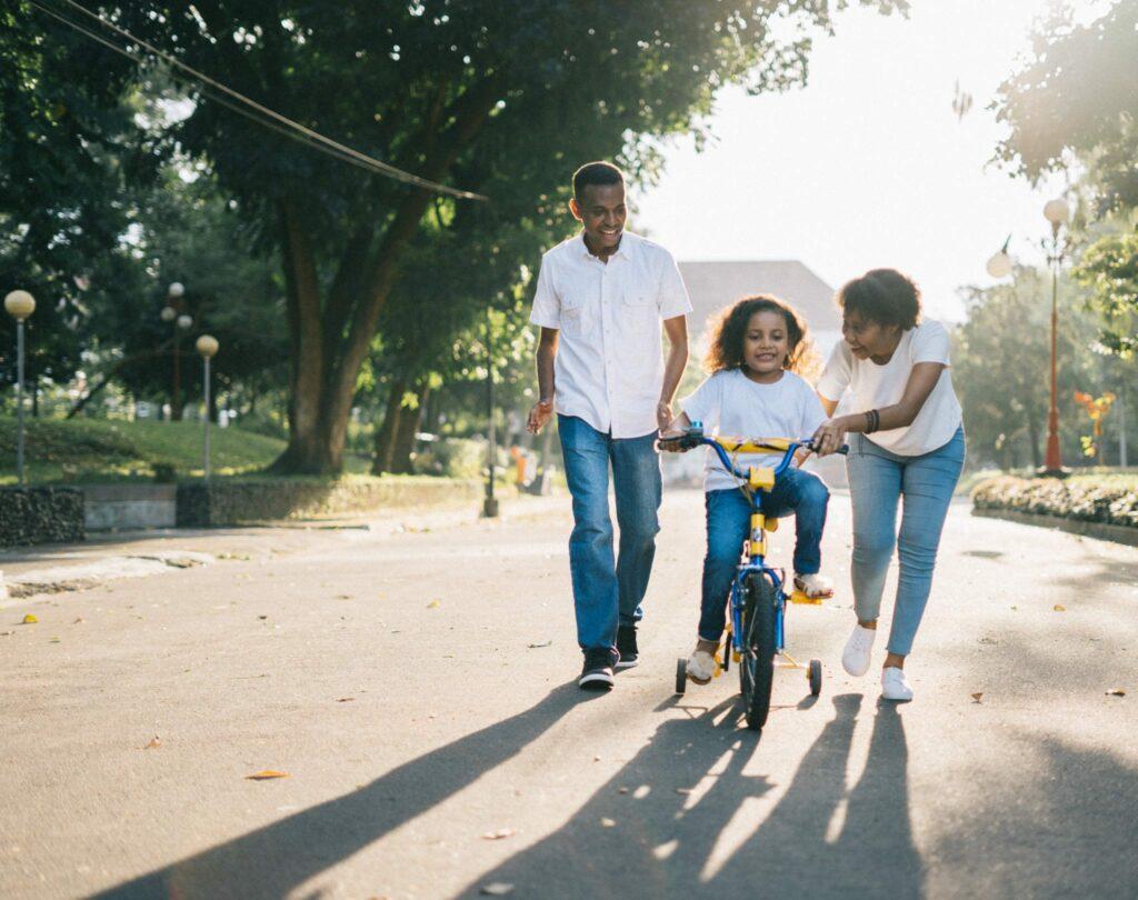 princípios para inspirar as famílias a brincar - Foto Agung Pandit Wiguna Unsplash - criança a aprender a andar de bicicleta com os pais