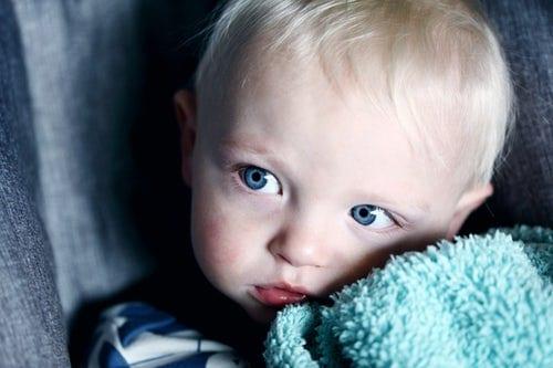 como acalmar as crianças - foto Unsplash - menino tapado por um cobertor com ar triste