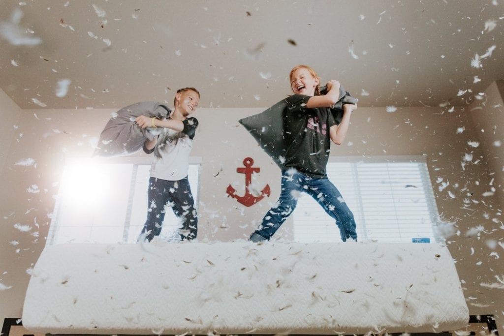 hiperatividade - foto unsplash - dois meninos a fazerem uma guerra de almofadas