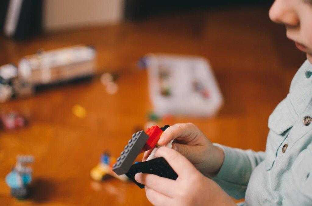 princípios para inspirar as famílias a brincar mais - Foto Kelly Sikkema Unsplash - criança a brincar com Lego e com brinquedos espalhados