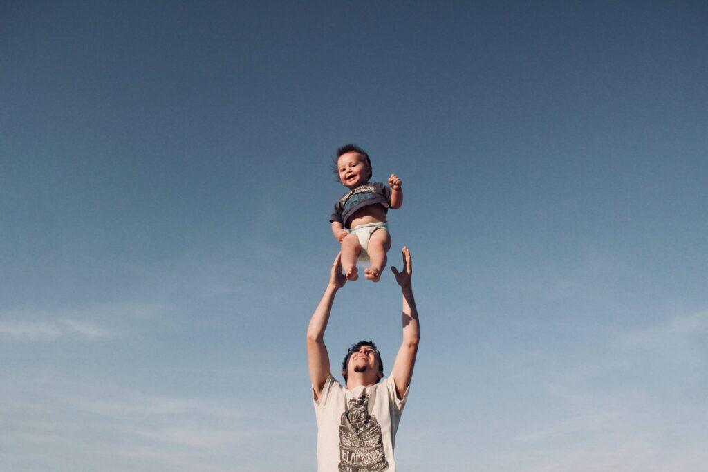 princípios para inspirar as famílias a brincar mais - foto pexels - pai a brincar com filho ainda bebé atirando-o ao ar enquanto ambos se riemprincípios para inspirar as famílias a brincar mais - foto pexels - pai a brincar com filho ainda bebé atirando-o ao ar enquanto ambos se riem