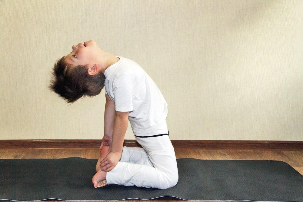 benefícios do yoga - foto stock - criança a fazer uma posição de yoga